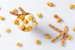 Gelado com caramelo e pipoca em uma tabela imagem de stock