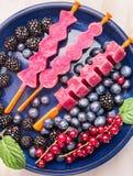Gelado cor-de-rosa dos picolés feito com as bagas frescas do verão: corinto vermelho, amoras-pretas, mirtilos no fundo de madeira Fotografia de Stock Royalty Free