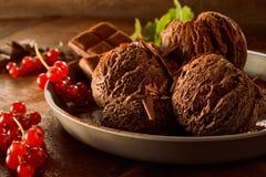 Gelado de chocolate com os corintos vermelhos no prato fotografia de stock royalty free