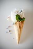 Gelado o immitation nas folhas e em flores decoradas cone de hortelã do waffle As peônias florescem no cone do waffle com folhas  Foto de Stock