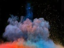 Gelanceerd kleurrijk poeder over zwarte Stock Afbeeldingen