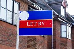 Gelassen durch Immobilienbürozeichen an den Häusern für Miete Lizenzfreie Stockfotos