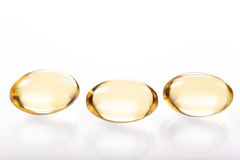 Gelatin capsules with fish oil on white background Stock Images