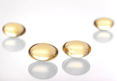 Gelatin capsules with fish oil on white background Royalty Free Stock Photography
