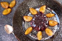gelatina fresca con i frutti e polvere decorata con le prugne ed il cucchiaio d'annata su un piatto scuro sulla fine di legno ner Fotografia Stock Libera da Diritti