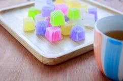 Gelatina variopinta croccante sul piatto di legno con tè Fotografia Stock
