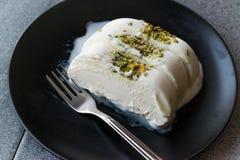 Gelato alla vaniglia di Maras del turco con la parte servita polvere del pistacchio in banda nera fotografia stock
