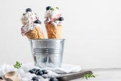 Gelato casalingo dei mirtilli nei coni della cialda e nel blueber fresco fotografia stock