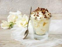 Gelato casalingo del limone o del burro spruzzato con i dadi ed il cioccolato in un vetro su un fondo di legno leggero Immagini Stock