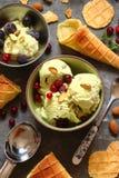Gelato con i pistacchi ed i coni gelati, con le bacche, min Fotografie Stock Libere da Diritti