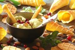 Gelato con i pistacchi ed i coni gelati, con le bacche, min Fotografia Stock