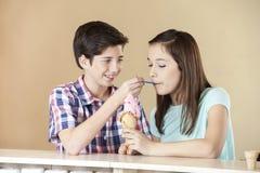 Gelato d'alimentazione della fragola del ragazzo alla sorella At Counter Fotografia Stock Libera da Diritti