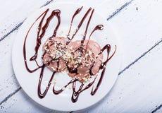 Gelato del cioccolato con gli anacardii e lo sciroppo di cioccolato Fotografie Stock