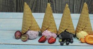 Gelato dolce in palle in un cono della cialda Bacche differenti e frutti di sapori stock footage