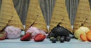 Gelato dolce in palle in un cono della cialda Bacche differenti e frutti di sapori video d archivio