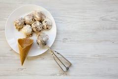 Gelato in piatto rotondo bianco con i coni dolci della cialda e cucchiaio per il gelato, vista superiore Da sopra, disposizione p Fotografia Stock