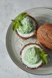 Gelato verde del sorbetto della menta nelle coperture della noce di cocco con le foglie verdi su un piatto su un fondo di pietra Immagini Stock