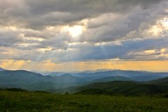Gelb blüht Sonnenuntergang über den rauchigen Bergen Lizenzfreies Stockbild