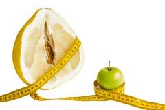 Gelb cutted frische rohe Pampelmuse und grünen Apfel mit Maßband herum stockfotografie
