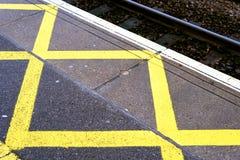 Gelb gemalte Bahnstations-Warnzeichen Stockfotos
