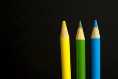 Gelb, grün und Blau färbten Bleistiftzeichenstifte auf einem schwarzen backgr Stockfotografie