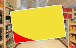 Gelb leeren Sie Aufkleber auf einem abstrakten Supermarkthintergrund Lizenzfreie Stockfotografie