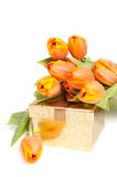 Gelb-orangee Tulpen, die auf ein goldenes Geschenk legen Lizenzfreie Stockfotos