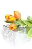 Gelb-orangee Tulpen, die auf ein Silbergeschenk legen Stockfotos