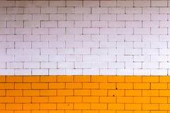 Gelb-orangee und weiße Backsteinmauer Die Farbwand hergestellt vom großen Größendekorations-Wandziegelstein und von keinem Vergip Stockfotografie