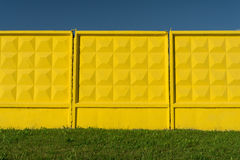 Gelb prägte konkreten Zaun, grünes Gras und blauen Himmel Stockbilder