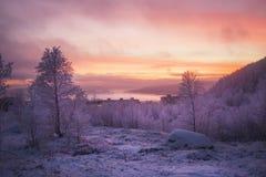 Gelb-rosa Sonnenuntergang über schneebedeckten Bergen, Wald, Häuser Stockfotos