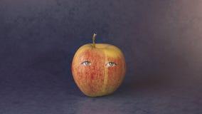 Gelb-rotes Apple mit Augen Stockfoto