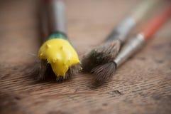 Gelbe Acrylfarbe auf Bürsten auf Holztisch backg Lizenzfreie Stockbilder
