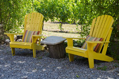 Gelbe Adirondack Stühle auf einem Patio Lizenzfreies Stockfoto
