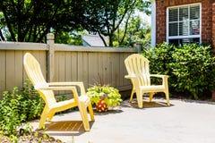 Gelbe Adirondack-Stühle auf Patio Stockfotografie