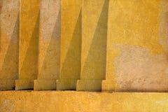 Gelbe alte schmutzige Betonmauerbeschaffenheit auf Altbau Stockbilder