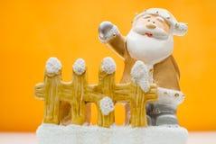 Gelbe alte Zeit Santa Claus-Figürchen, die hinter Gartenzaun steht und mit einer Hand wellenartig bewegt Lizenzfreies Stockfoto