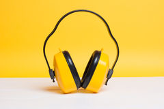 Gelbe arbeitende schützende Kopfhörer auf Gelb stockbild