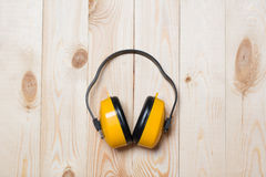 Gelbe arbeitende schützende Kopfhörer auf Holztisch stockbild
