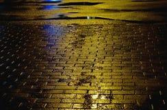 Gelbe Asphaltoberfläche mit Pfützen und Pflasterstein Regnen des Wetters Stockfoto