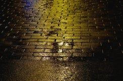 Gelbe Asphaltoberfläche mit Pfützen und Pflasterstein Regnen des Wetters Lizenzfreie Stockfotos