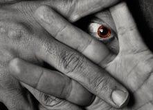 Gelbe Augenanstarren throug Finger Lizenzfreie Stockfotos