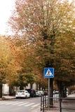 Gelbe autmn Bäume entlang der Straße und dem Zebrastreifen unterzeichnen Stockbilder