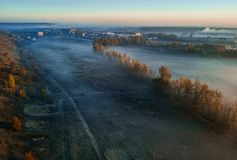 Gelbe Bäume des Herbstes und nebeliges blaues Tal SONNENAUFGANG Stadt am Hintergrund Warme und kalte Farben der Fallstimmung stockbilder