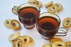 Gelbe Bagel und Schalen schwarzer Tee Stockbild