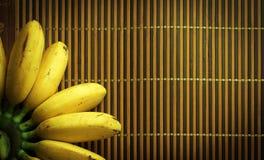 Gelbe Banane auf hölzerner Matte Stockfotografie