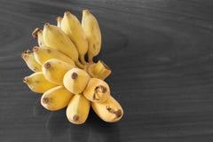 Gelbe Banane mit hölzernem Beschaffenheitsschwarzweiss-hintergrund, Beschneidungspfad, Kopienraum Stockfotos