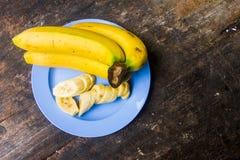 Gelbe Bananen reifen gedient mit dem Hintergrund ist ein hölzerner Schreibtisch Lizenzfreies Stockbild