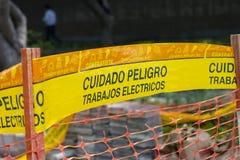 Gelbe Bandmarkierungsvorsicht 'cuidado 'auf spanisch lizenzfreies stockfoto