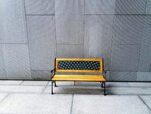 Gelbe Bank auf weißem oder grauem Betonmauerhintergrund Stockfoto
